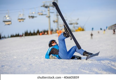 Young girl skier in blue ski suit after the fall on mountain slope against ski-lift. Ski resort at Carpathian Mountains, Bukovel, Ukraine. Winter sports concept.