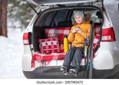 Young girl skier sitting in car boot compartment and drinking hot tea from cup. Winter park