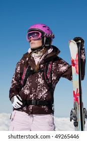 Young girl skier with skis wearing sport gear. Winter vacation
