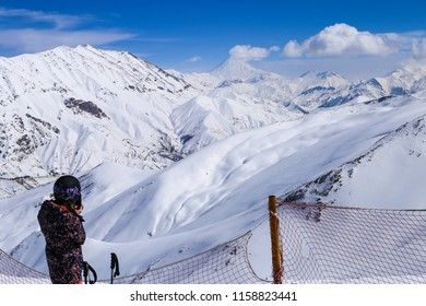 a young girl skier is watching beautiful landscape view of mountain and damavand peak covered with snow from dizin ski resort top peak.