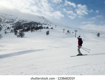 Young girl skiing with blue sky and blizzard in the background
