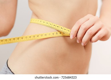 A young girl in a skirt measures the waist, weight control, monitors the figure