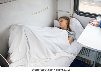Young girl sleeping on the bottom shelf in the second-class train carriage
