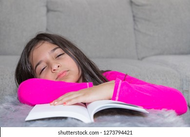 A young girl is sleeping while doing her homework