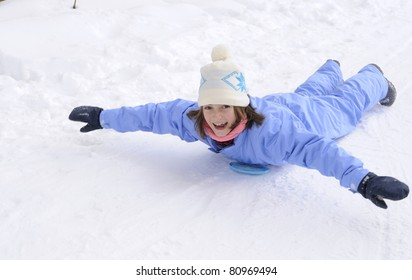 Young girl sliding in the snow