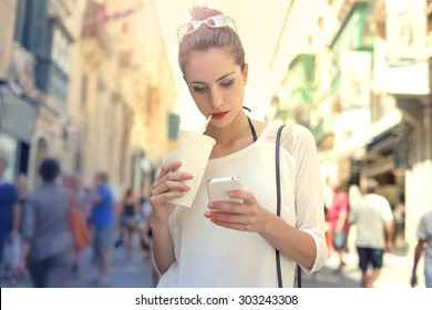 Young girl with smartphone and soft drink