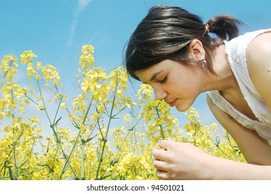 A young girl smelling a canola spring flower.