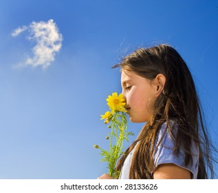 young girl smelling yellow wild flowers