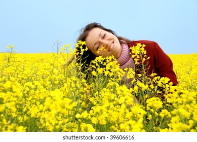 The young girl smells yellow flowers in the field