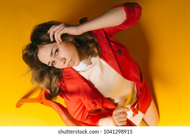 young girl with a smile on her face posing in a red spring cloak on a paper colored background. emotional portrait of a student. long hair and clean skin