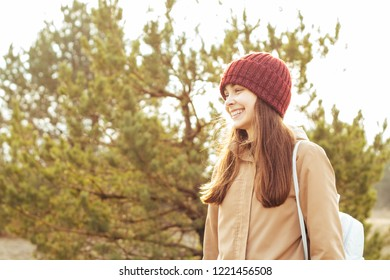 A young girl smiles against the background of the forest. The concept of travel and adventure. copy space.
