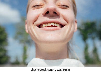 young girl smiles and shows her crooked teeth in close-up. concept: dental displacement due to injuries and poor care, oral hygiene and dental health. problem skin of a teenager
