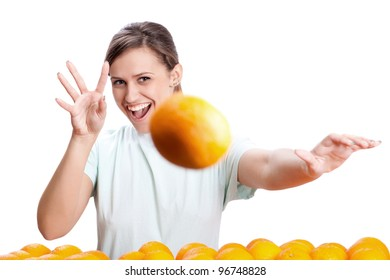 young girl smiles and throws oranges
