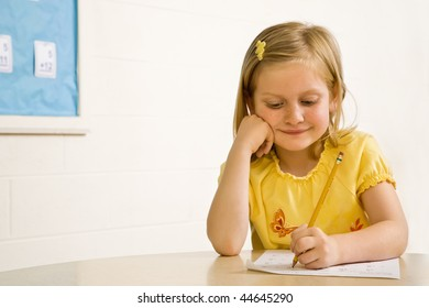 Young girl smiling in classroom writing on paper. Horizontally framed shot.