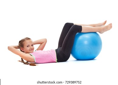 Young girl smiling and doing sit ups with a large gymnastic ball - strength and vitality concept, isolated