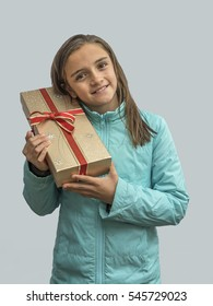 a young girl smiling face and eyes with a gift for christmas or new year advertising model