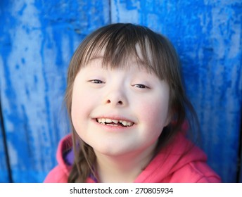 Young girl smiling on background of the blue wall.