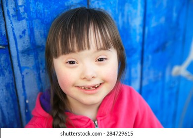 Young girl smiling on background of the blue wall