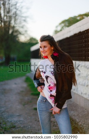 c64a0ba6d Young girl smiling and posing in rock black leather jacket casual stand-up  background of