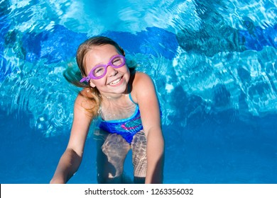Young girl smiling in swimming pool on summer vacation at camera