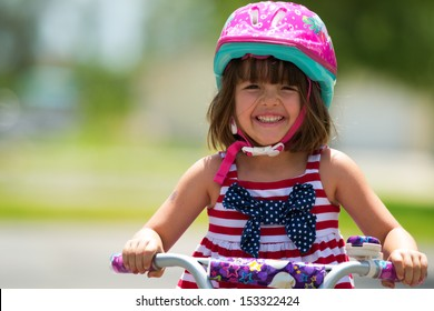Young girl smiling while riding a bicycle.