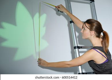 young girl smiling while using a measuring green leaf decoration on the wall with tape tool. Studio shot.