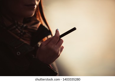 Young girl smokes electronic cigarette outdoor at sunset in spring.Female model smoking ecig device outside.Bad habit and unhealthy lifestyle concept