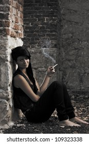 Young girl smoking on ruined building