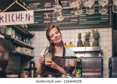 Young girl with smoothie in the kitchen