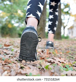 Young girl in sneakers on her feet, walks through the fall leaves on the road in the woods in the sunshine outdoors