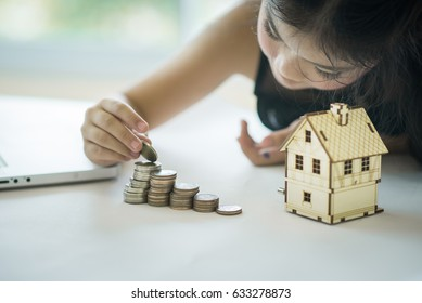 Young girl sorting,grouping her coins on table with laptop beside.Young girl counting her money on her table with laptop.Young girl saving a money.Girl's creativity,imagination.
