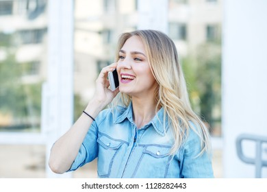 Young girl speaks on the phone in the street. Concept of life style, urban, work.