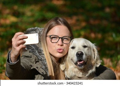Young girl with spectacles posing and taking selfie with her golden retriever dog
