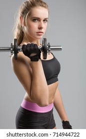 young girl in sport outfit with a barbell