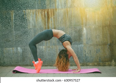 Young girl in sportswear doing on the street sports fitness exercises, yoga, urban style