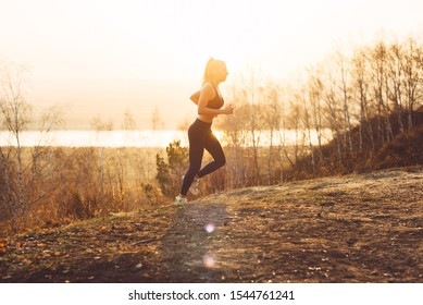 Young girl in sportswear jogging in nature in the sun