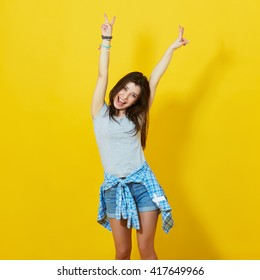 Young girl spreading hands with joy isolated on bright yellow background. Carefree teenage woman posing in studio over vivid yellow wall