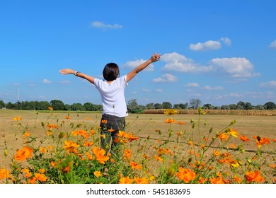 Young girl spreading hands with joy and inspiration in the flower garden , freedom concept. Free Happy Woman Enjoying Nature. Beauty Girl Outdoor. Enjoyment.