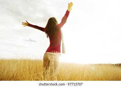 Jovem espalhando as mãos com alegria e inspiração de frente para o sol