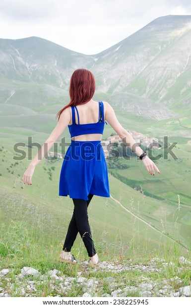 Young girl spreading hands with joy and inspiration in the mountain landscape
