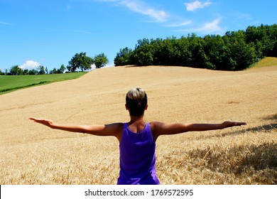 Young girl spreads her arms in the wheat field on the blue sky background. Female back view.