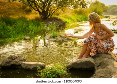 a young girl sprinkles water near the lake