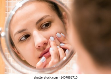 Young girl squeezes pimple on the fer face in front of a bathroom mirror. Beauty skincare and wellness morning concept.