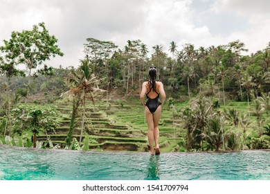Young girl stand on the edge of infinity pool with a view on rice terrace. Travelling to Ubud, Bali, Indonesia