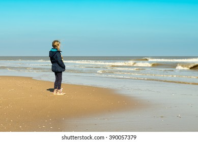 A young girl standing alone at the beach looking at the waves / Alone at the beach