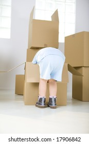 Young girl standing beside cardboard boxes. She's bending to one box.