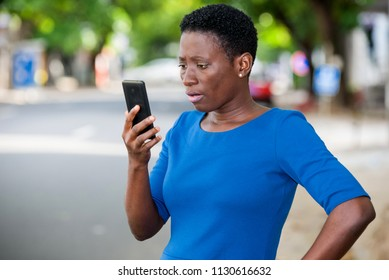 young girl standing in blue camisole looks at mobile phone with surprised look.