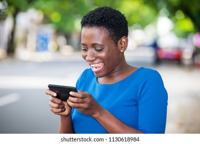 young girl standing in blue camisole is watching mobile phone while laughing.