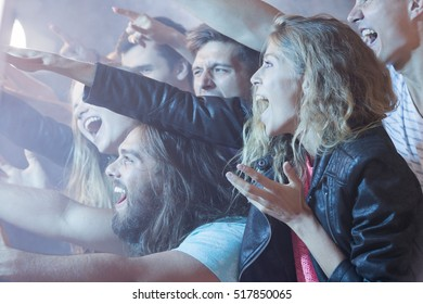 Young girl standing in a crowd of people, having fun at a rock concert