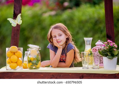 Young girl standing at her lemonade stand in the garden at sunny day